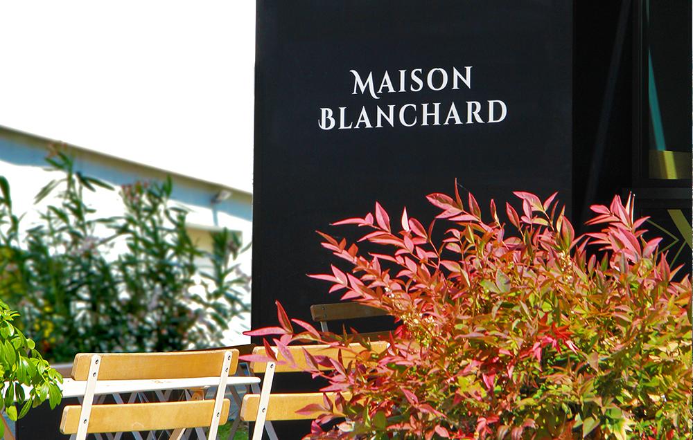Photographie d'un détail de la boutique, vue sur la terrasse, le logo Maison Blanchard en blanc sur la boulangerie noire